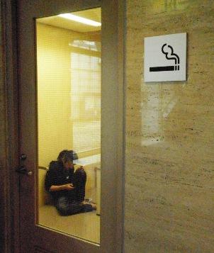 音響の渡邉禎史さんが喫煙室の中で座っている画像